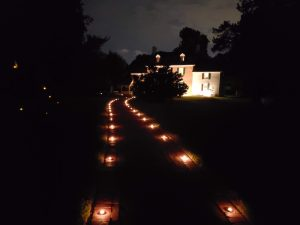 a house shown with a lighted driveway