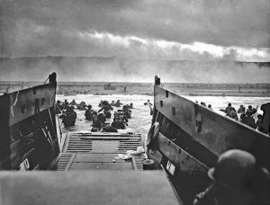 image shows soldiers getting off a boat onto a beach